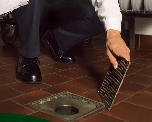 Rvisión de sumideros para prevenir plagas en una cocina de restaurante